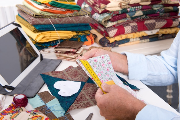 Styliste homme mesurant un morceau de tissu
