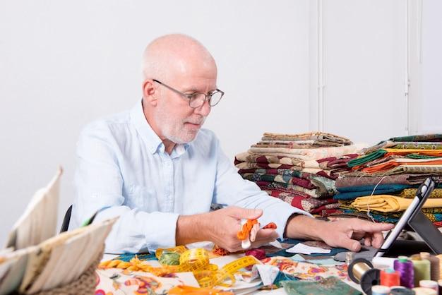Styliste homme travaillant avec une tablette