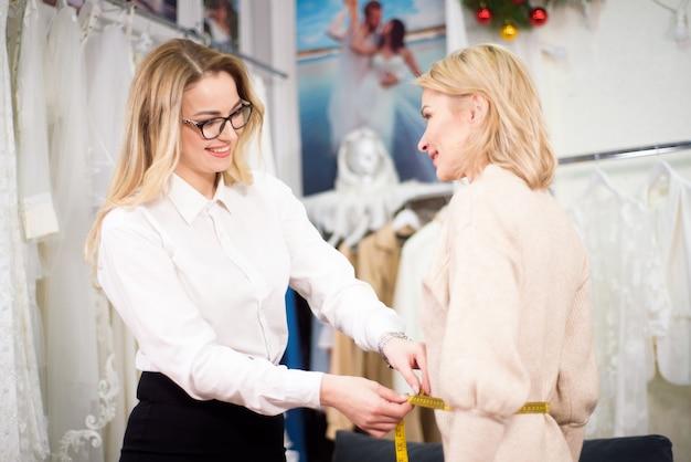 Styliste sur mesure femme prenant la mesure avec une fille modèle. concept coudre des vêtements.