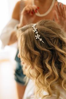 Le styliste met une épingle à cheveux dans la coiffure de la mariée lors des préparatifs de mariage