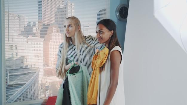 Styliste de mode féminine proposant des vêtements différents de modèle noir pour la séance photo