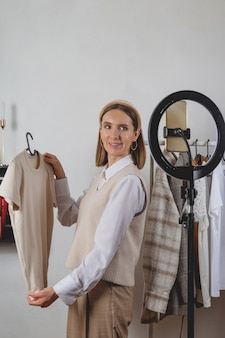 Styliste de mode femme millénaire enregistre une vidéo de mode sur smartphone avec lampe à anneau