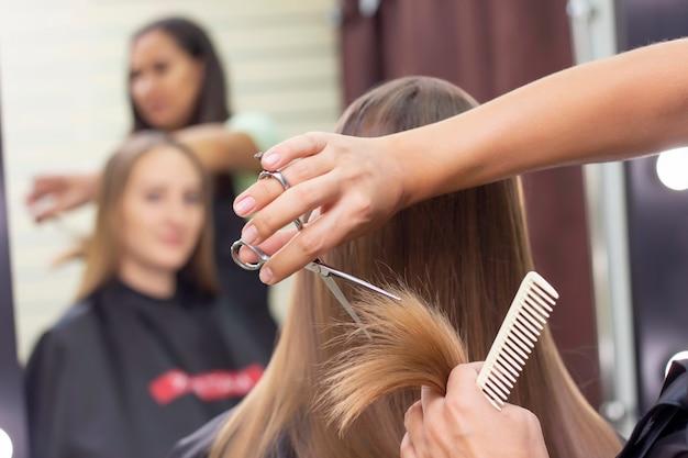 Un styliste professionnel coupe les cheveux des femmes dans le salon