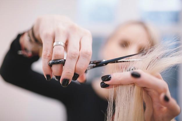 Styliste professionnel taillant les pointes de cheveux