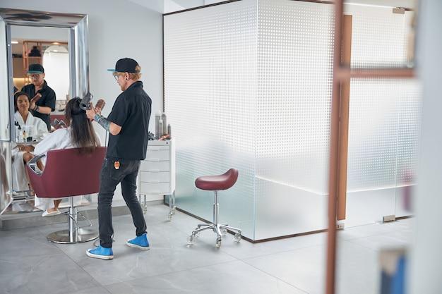 Styliste utilisant des outils et faisant bien paraître les cheveux