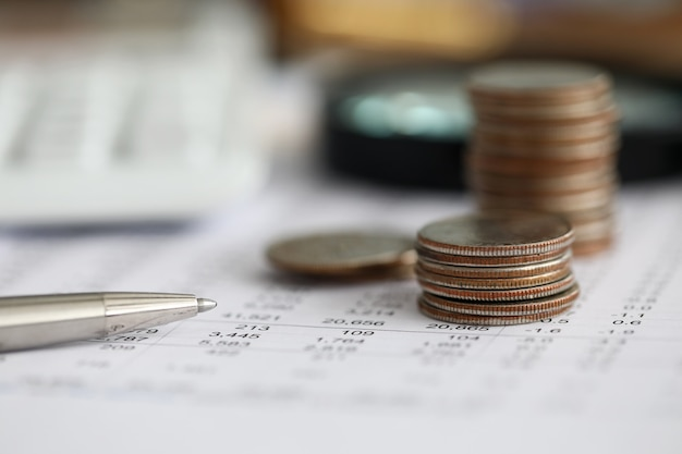 Stylo argent couché sur du papier de statistiques financières avec un ensemble de chiffres