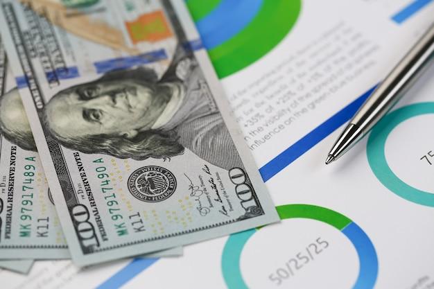 Stylo argent couché sur des parcelles de dollars en espèces de bureau