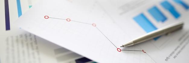 Le stylo argenté repose sur des documents