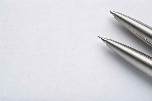 Stylo à bille en métal et crayon automatique sur fond de papier blanc avec espace de copie