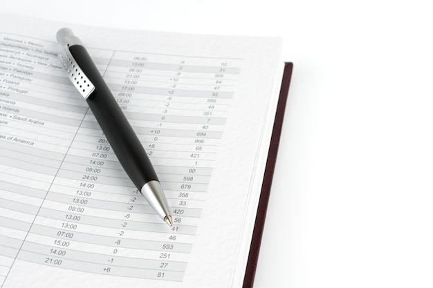 Stylo à bille noir sur un calendrier de page. sur la table.