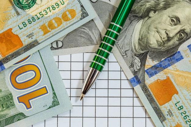 Un stylo à bille repose sur cent dollars avec une image de franklin sur la surface en damier.