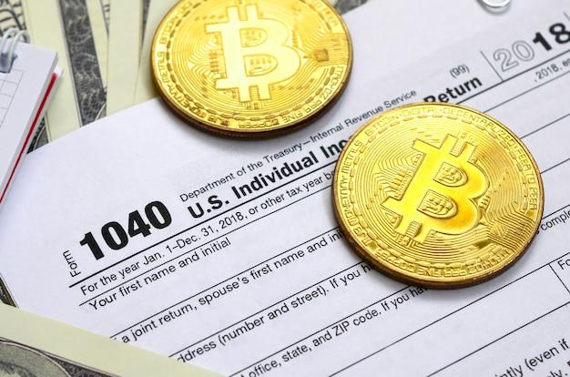Le stylo, les bitcoins et les billets d'un dollar se trouvent sur le formulaire d'impôt 1040 us déclaration de revenus des particuliers. le temps de payer des impôts