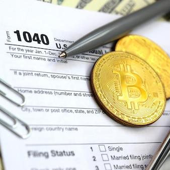Le stylo, les bitcoins et les billets d'un dollar se trouvent sur le formulaire d'impôt 1040 us