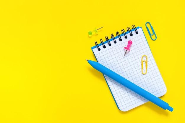 Stylo bleu et bloc-notes ouvert avec une feuille vierge sur une surface jaune