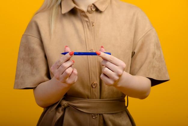 Stylo bleu en main de femme isolée sur jaune.
