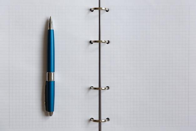 Un stylo bleu se trouve sur une feuille blanche d'un ordinateur portable. cahier d'école carré ouvert à plat