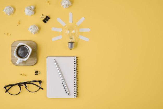 Stylo, bloc-notes, lunettes de vue, tasse de café, ampoule sur fond jaune.