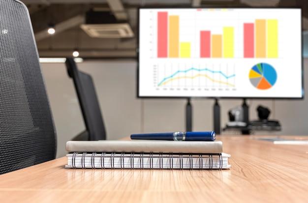 Stylo et bloc-notes sur table avec fond de télévision de présentation graphique maquette dans la salle de réunion