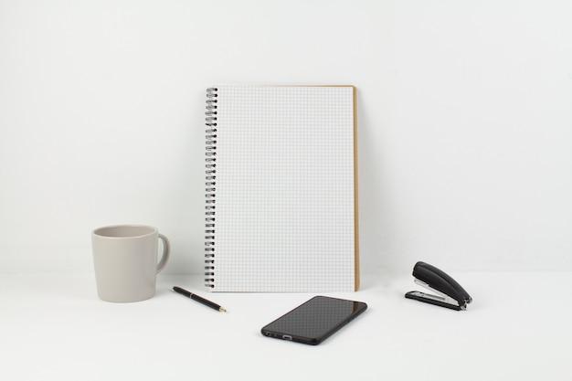 Un stylo avec bloc-notes et tasse au bureau