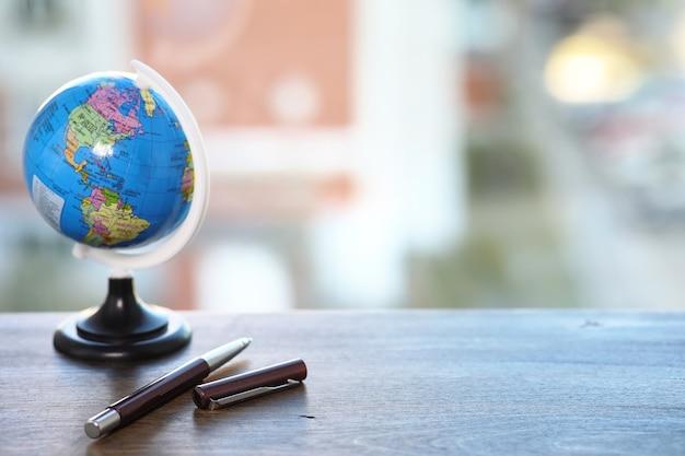Un stylo sur le bureau et un petit globe bleu