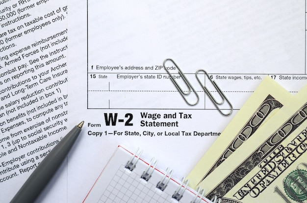 Le stylo, le cahier et les billets d'un dollar se trouvent sur le formulaire d'impôt w-2 déclaration de salaire et d'impôt