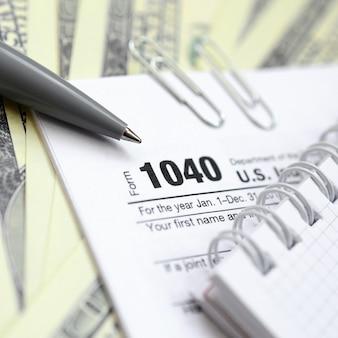 Le stylo, le cahier et les billets en dollars se trouvent sur le formulaire 1040 déclaration de revenus des particuliers américains. le temps de payer des impôts