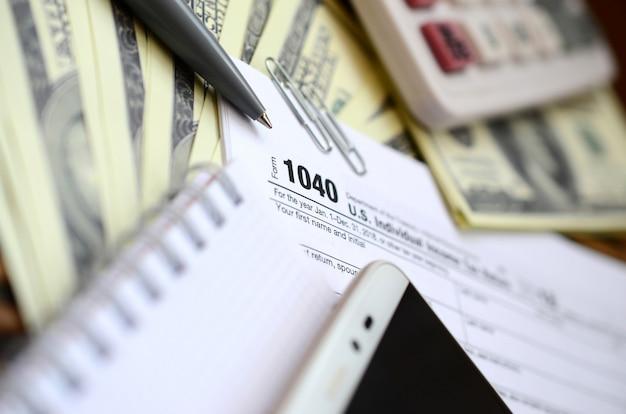 Le stylo, le cahier, la calculatrice, le smartphone et les billets d'un dollar