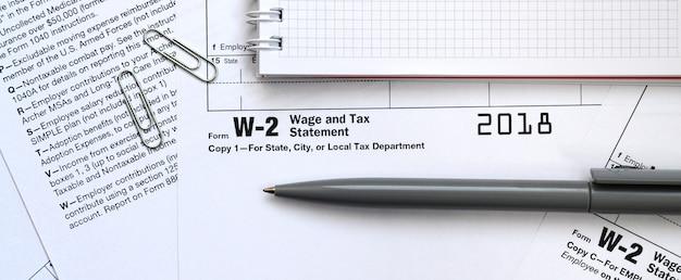 Le stylo et le cahier figurant sur le formulaire de déclaration d'impôt w-2. le temps de payer des impôts