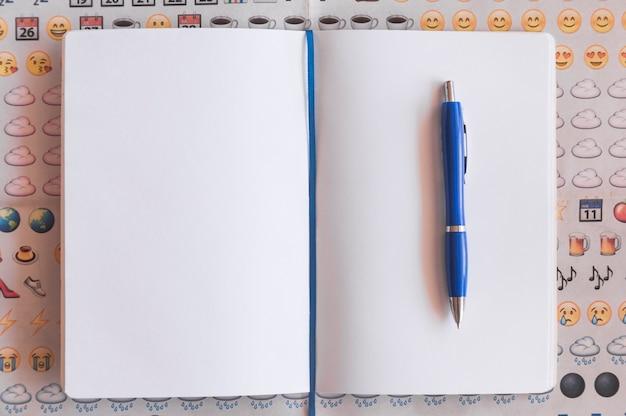 Stylo et cahier sur fond d'emoji