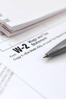 Le stylo et le cahier sur le formulaire d'impôt w-2 déclaration de salaire et d'impôt. le temps de payer des impôts