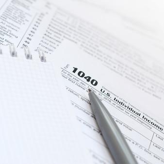 Le stylo et le cahier se trouvent sur le formulaire fiscal 1040 déclaration de revenus des particuliers américains. le temps de payer des impôts