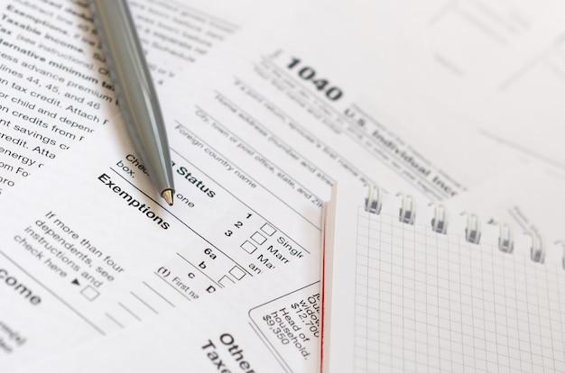 Le stylo et le cahier se trouvent sur le formulaire fiscal us individual