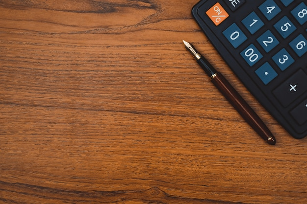 Stylo avec calculatrice sur fond en bois