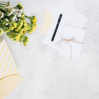 Stylo et cartes de vœux près du bouquet et du cadeau