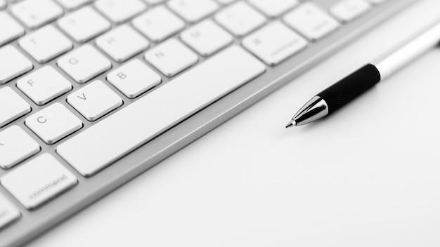 Stylo et clavier sur fond de bureau blanc.