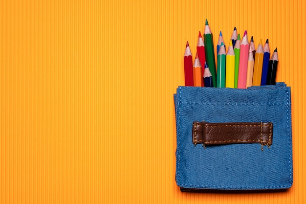 Stylo de couleur dans un mini-sac sur fond orange.