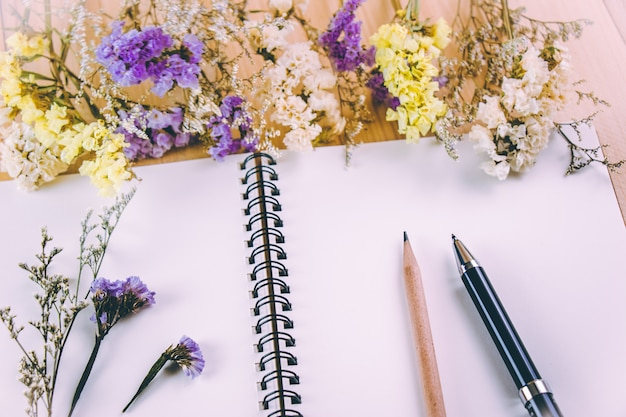 Stylo et crayon mettre sur un cahier vierge près de bouquet de fleurs, sur une table en bois