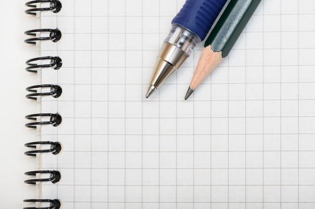 Stylo et crayon de plomb sur une page vierge du cahier