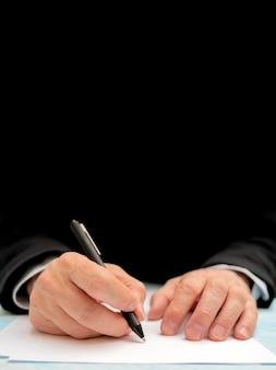 Un stylo dans la main d'un homme. feuille de papier blanc signer un document.