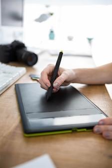 Stylo dessin sur une tablette à dessin numérique au bureau