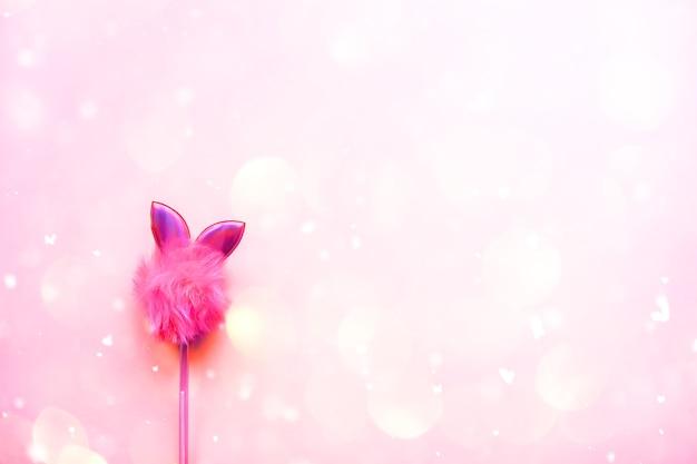 Stylo drôle sur fond pastel rose tendre. objet de papeterie scolaire moderne et coloré.