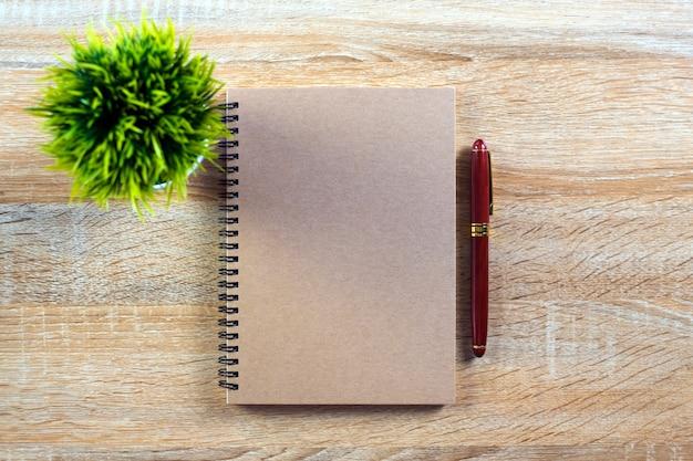 Stylo à encre avec papier pour ordinateur portable et petit arbre de décoration sur bois