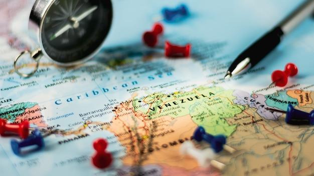 Stylo et épingle sur la carte du monde.