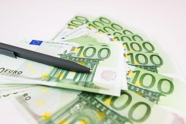 Stylo gris sur billets de 100 euros. beaucoup d'argent sur blanc. notion financière.