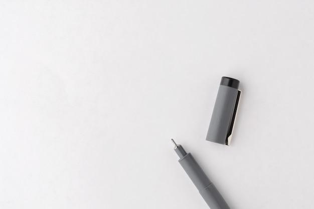 Un stylo gris sur une feuille de papier blanche vierge