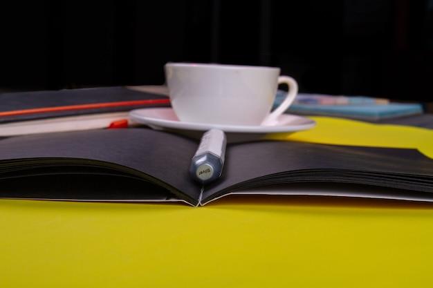 Stylo gros plan sur le livre avec une tasse de café blanche.