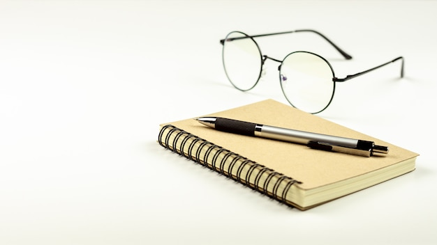 Stylo sur livre de journal et lunettes sur fond de bureau blanc.