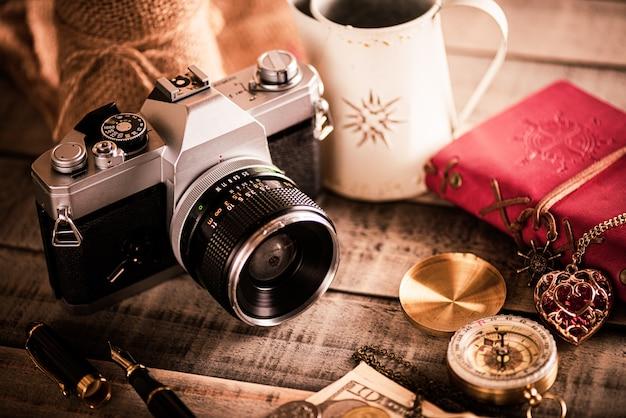 Stylo livre rouge, argent pièces de monnaie, boussole et appareil photo argentique rétro sur bois.