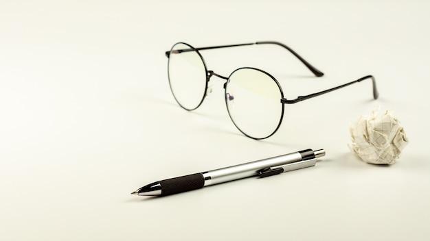 Stylo avec des lunettes et une boule de papier froissé sur fond de bureau blanc.