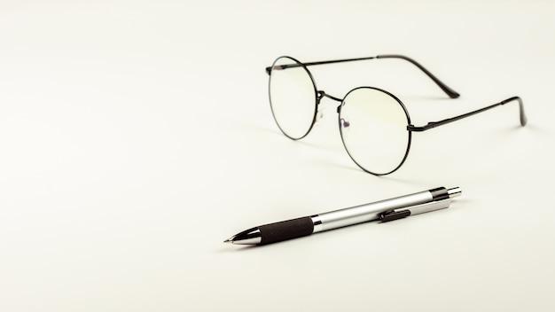 Stylo et lunettes sur fond de bureau blanc.